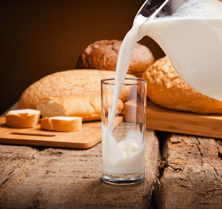 Milk in a glass closeup with bread photo