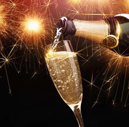 botella champagne: Feliz año nuevo, champán con luces de bengala en el fondo oscuro
