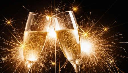 botella champagne: Copas de champán y luces de bengala en el fondo brillante con luces de bengala