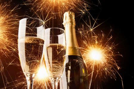 brindisi champagne: Felice anno nuovo, champagne con stelle filanti su sfondo scuro