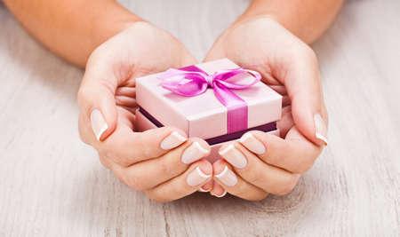 女性の手の中の小さな贈り物をクローズ アップ