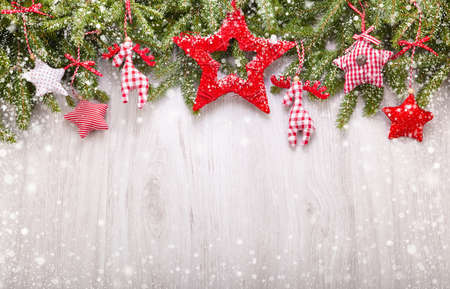 Snow-covered fir branches and Christmas decorations on light wooden background