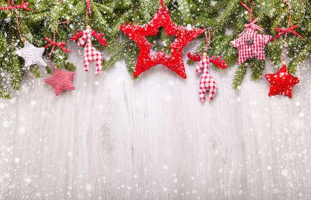Zasněžené jedle větve a vánoční ozdoby na světlém dřevěném pozadí
