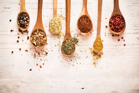 curry spices: Spices in wooden spoons on white wooden background