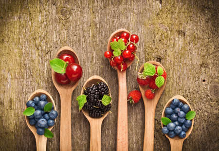 Berries in wooden spoons on wood texture