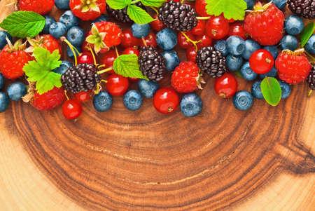 juicy: Fresh juicy berries with green leaves on wood texture
