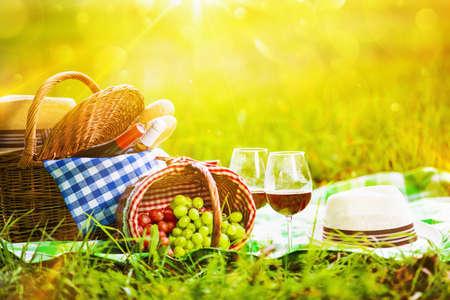 canastas con frutas: Picnic con vino y uvas en la naturaleza. En la luz del sol