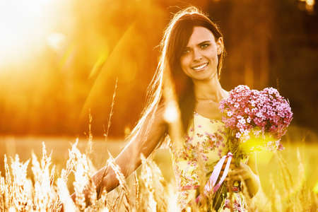 women smiling: Beautiful girl with flowers on sunny background