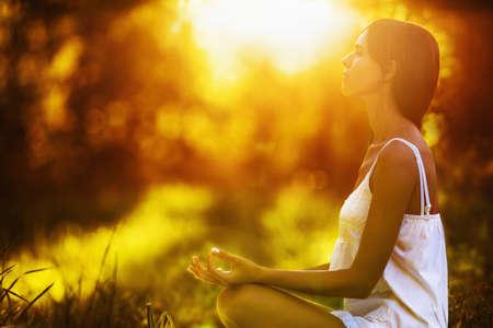 Yoga vrouw mediteren bij zonsondergang. Vrouwelijk model mediteren in serene harmonie Stockfoto