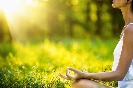 夕暮れ時瞑想ヨガ女性。女性モデルの穏やかなハーモニーで瞑想
