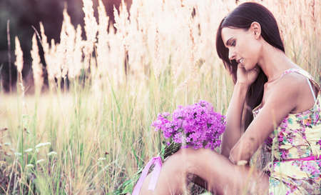 green and purple: Beautiful girl with summer flowers sitting in a field