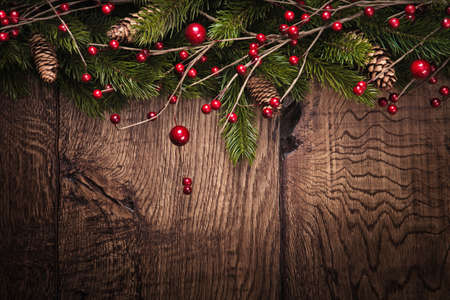 christmas trees: Christmas background with fir branches and berries on wood background