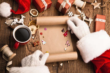 cartas antiguas: Santa Claus con los regalos y la lista de artículos deseados en mesa de madera