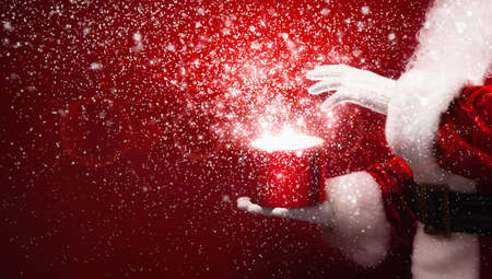 present box: Santa Claus with magic box and snow on red background