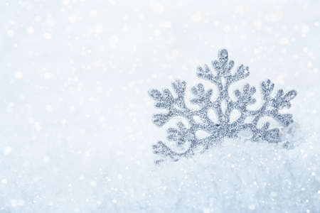 crystal background: Snowflake on white snowy background with bokeh effect Stock Photo