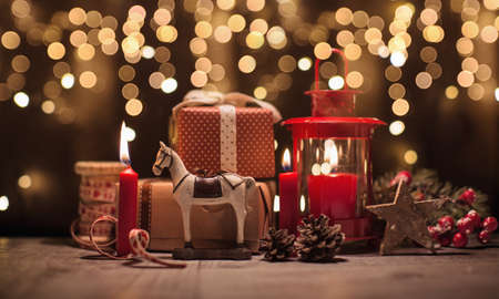 candle: Christmas gifts and toys on bokeh effect background. Christmas decorations