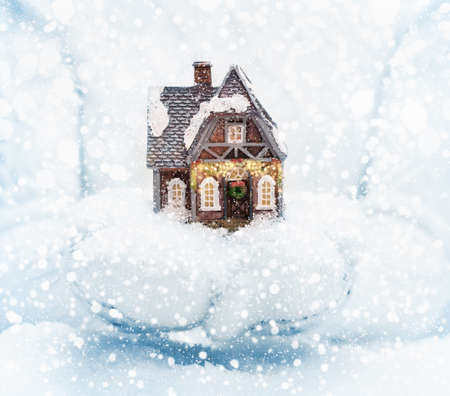 christmas house: Christmas house in female hands on snowy background Stock Photo