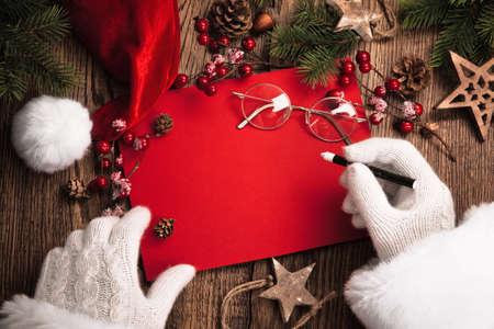 Santa Claus s dárky a červenou kartou na dřevěném stole Reklamní fotografie