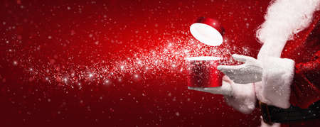 opening gift: Santa Claus with magic box and snow on red background