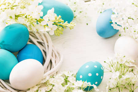 Easter decoration with eggs and flowers on white wooden background