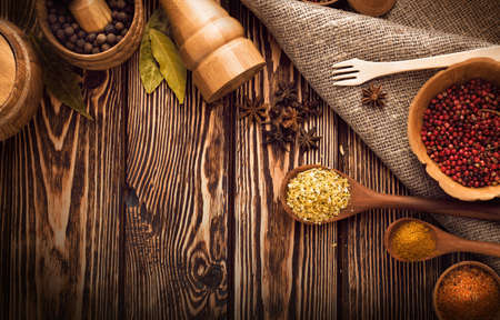 spicy cooking: Pepper, curry and other spices on wooden background