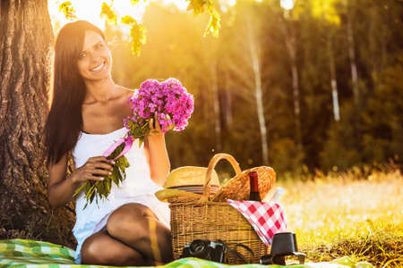 nature of sunlight: Young happy girl with flowers on nature in sunlight
