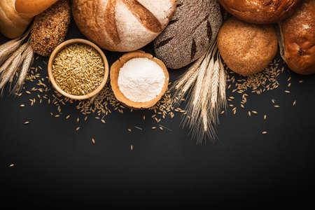 Pan fresco y trigo sobre fondo negro Foto de archivo