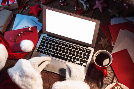 christmas hat: Santa Claus working on computer. Open laptop with white screen concept