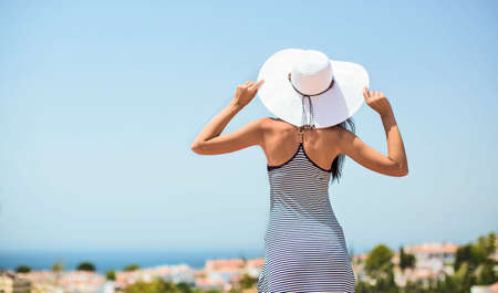 admires: Beautiful girl in hat admires view of the sea Stock Photo