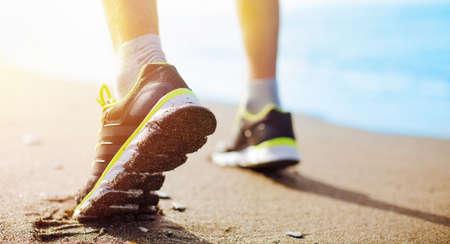 Runner feet running on the coast closeup on shoe. Sport concept