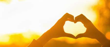 Silhouette Hand Herzform mit Sonnenlicht. Weibliche hände