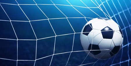 Fußball in Tor auf blauem Hintergrund Lizenzfreie Bilder