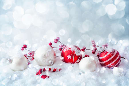 Christmas decorations with balls and sparkling snow on light blue background