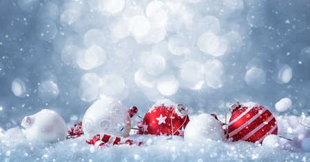 Winter decorations on snow covered sparkling background