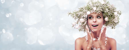 Beauty Fashion Model Girl with Fir Branches Decoration. Winter Hairstyle and Make Up