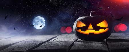 Jack O Lanterns Glowing At Moonlight In The Spooky Night. Halloween Pumpkins Background Standard-Bild - 107306513