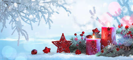 Christmas Decorations With Candles On a Snowy Background Stock Photo
