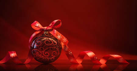 Red Christmas Ball with Ribbon and Bow on Red Background With Reflection Standard-Bild - 107941719