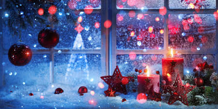 Winter Decoration With Candles Near The Snow-Covered Window. Christmas Background Standard-Bild - 108039642