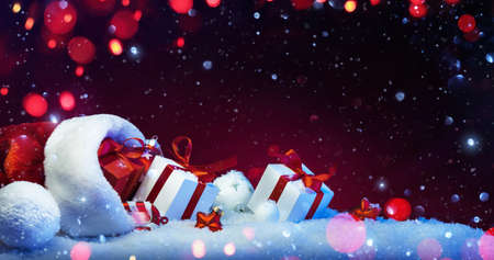 Holidays Decoration with Christmas Gifts on a Red Background with Colored Lights and Snow Effects Standard-Bild - 109103404