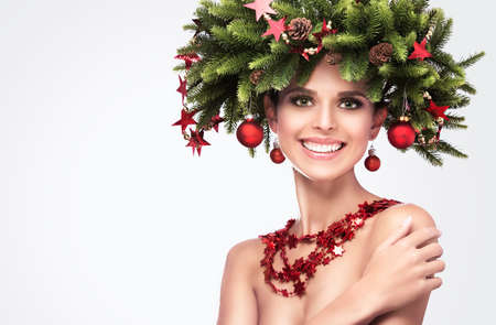 Smiling Beauty Fashion Model Girl with Fir Branches Decoration. Winter Hairstyle and Make Up Isolated Standard-Bild - 109170295