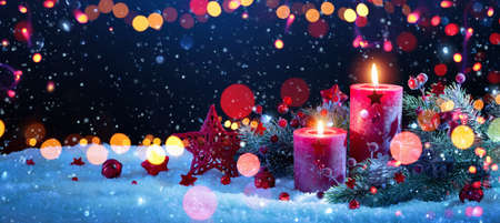 Christmas Decorations With Candles On a Snowy Background with Colored Lights Effects