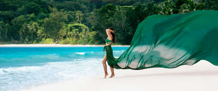 Beautiful Woman with Flying Fabric of Emerald Color on the Coast of the Ocean. Tropical Island Standard-Bild - 116011011