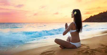 Yoga Concept. Woman Practicing Lotus Pose on Beach Standard-Bild - 116011018