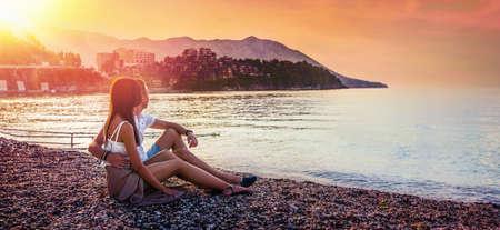 Happy Couple Sits on the Sea Coast at Sunset. Summer Travels Standard-Bild - 116011021