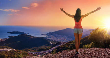 Happy Woman in the Mountains Looking at the Sunset with Open Hands Standard-Bild - 116011022
