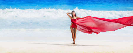 Beautiful Woman with Flying Fabric of Red Color on the Coast of the Ocean Standard-Bild - 116011985