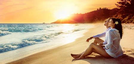 Happy Couple Sits on the Ocean Coast at Sunset. Summer Vacation Standard-Bild - 116011986