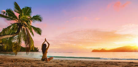 Yoga Concept. Woman Practicing Lotus Pose on Beach Standard-Bild - 116011993
