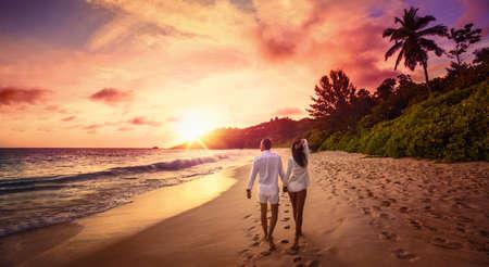 Jonge gelukkige geliefden op het strand. Paar wandelen op romantische reizen Huwelijksreis Vakantie Zomervakantie Romantiek Zonsondergang